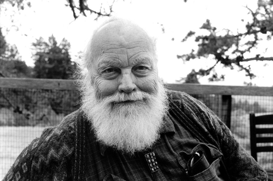 Lou Harrison seated on a deck, smiling at the camera with a bald head an a fluffy white beard.