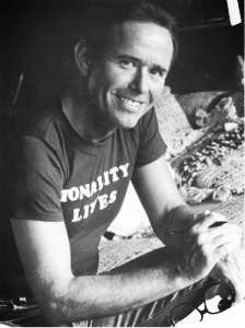 """A young David Del Tredici with a pen and his glasses in hand, wearing a t-shirt that says """"Tonality Lives"""""""