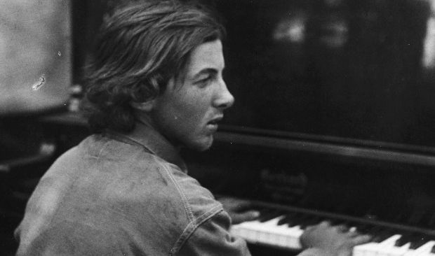 A young Henry Cowell with shaggy hair, at the piano.