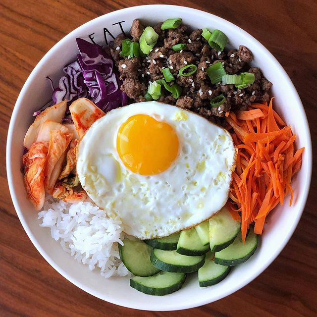Korean Inspired beef bowl for dinner tonight. This is such an easy throw together meal - especially when you buy pre shredded and cut veggies. Basically this is just one big assembly bowl 🍲🍲🍲 Korean ground beef, rice, kimchi, cabbage, carrots, cucumbers, and a fried egg to top it all off!!! . . . How I made the beef...👇🏻 . . When I say a total throw together, I just mean using what I had on hand in my kitchen. . . 1️⃣First, with a skillet on medium heat, break up and brown lean ground beef. Set it aside.  2️⃣Then in a small bowl, I combined fresh ginger, minced garlic, coconut aminos, a little sesame oil, fresh squeezed orange juice, and Mikes hot honey* - yes I just eyeballed, and tasted as I went, so I don't have exact measurements for this one. I'd say adjust to your liking!  3️⃣Whisk the marinade together, then pour it in the skillet, letting it bubble a bit and thicken before putting the ground beef back into the skillet.  4️⃣Continue to cook until beef is coated and heated through. That's it! So delish! (Note* you could use brown sugar also, @mikeshothoney was the only sweetener I had on hand, and it gave it a nice kick, so I used that)