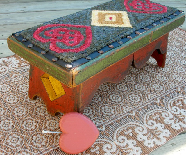 The finished footstool shown with a wooden heart carved by my husband, Art.
