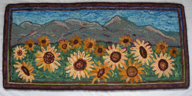 Sunflowers for Sarah , is a rug I designed for my daughter-in-law. It features Grizzly Peak in the background, which can be seen from the back of their home.