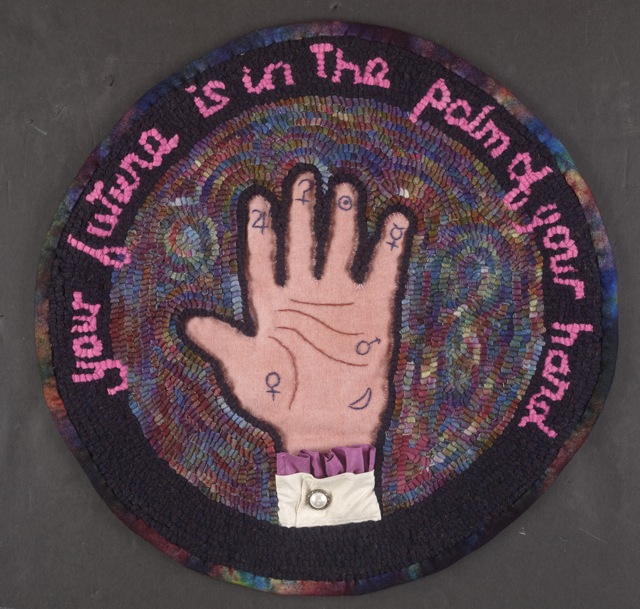 """Fickle Finger of Fate,  16"""" diameter. Wool cloth strips, embroidery, trapunto, silk and button embellishment on linen foundation. Photo by Impact Expozures."""