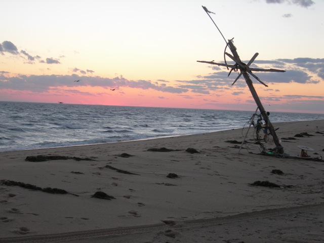 Sunset on Race Point at the curved tip of Cape Cod.  Here is where East coast-ers can see the sun set over water.  Someone made artwork from scavenged beach detritus.