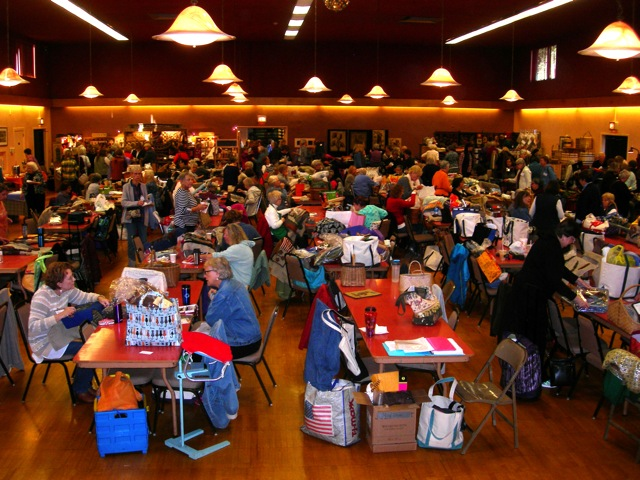 This is a room filled with people focused on rug hooking and having fun.