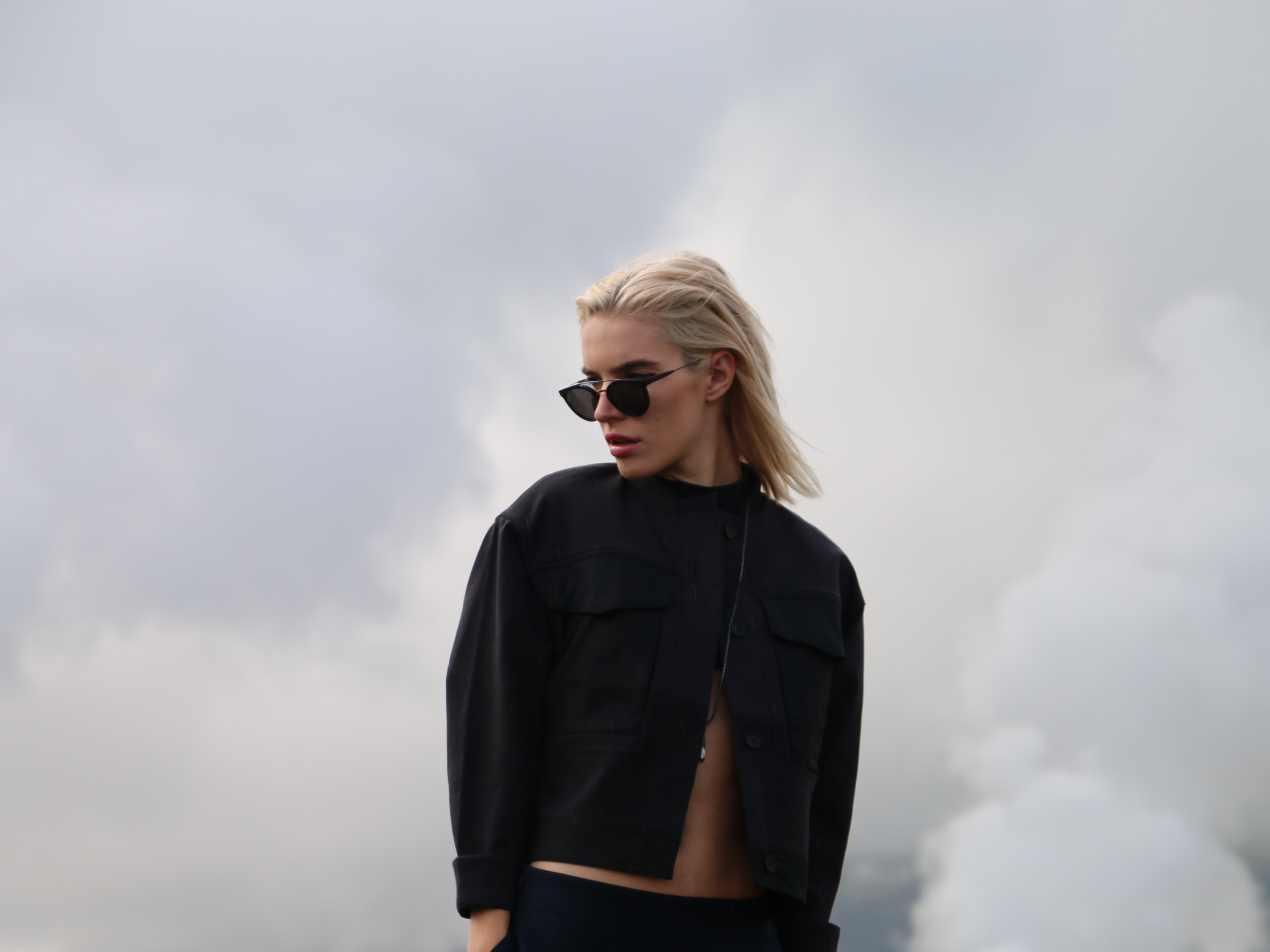 Chloe is wearing GIAGUARO FEMMENA Sunglasses by RETROSUPERFUTURE Cropped Flight Jacket + Front of a Line Skirt by Kit and Ace, JERN X ANTIQUED STEEL Pendant by Vitaly