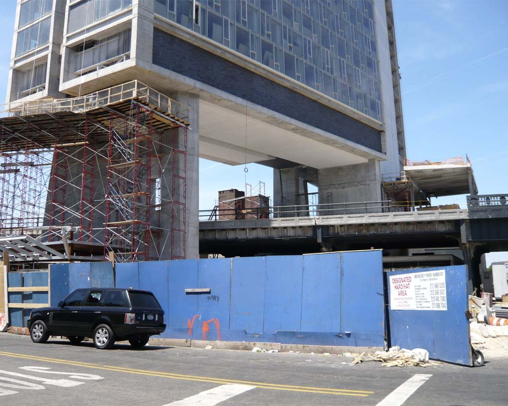 Renovating the structure of the High Line in 2008, prior to its reinvention as a park. The Standard Hotel is under construction over and above the rail line.