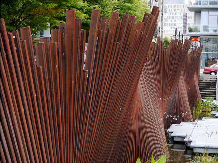 The patina, colour and waving form of this weathered steel screen all create a sinuous, dynamic texture.
