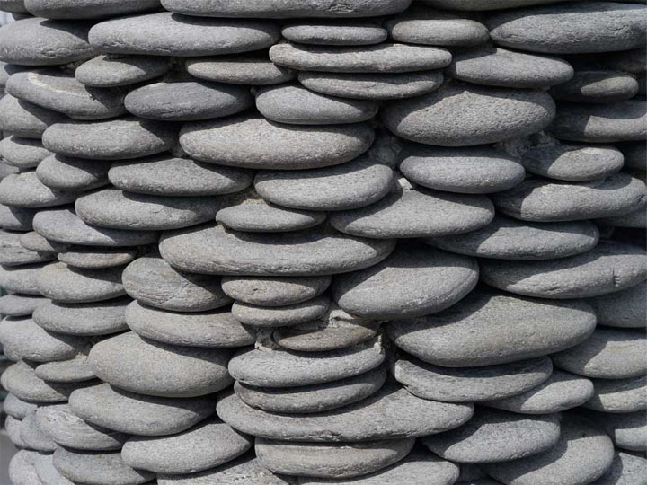 The column is encircled in pebbles that look as if they're precariously balanced on top of each other: they're smooth so you want to touch, but it looks risky!