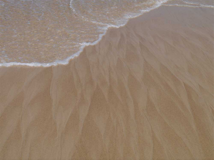 The softness of wet sand washed into braided wave patterns.