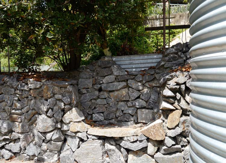 This dry stacked stone seat is integrated into a retaining wall near the front of the property.