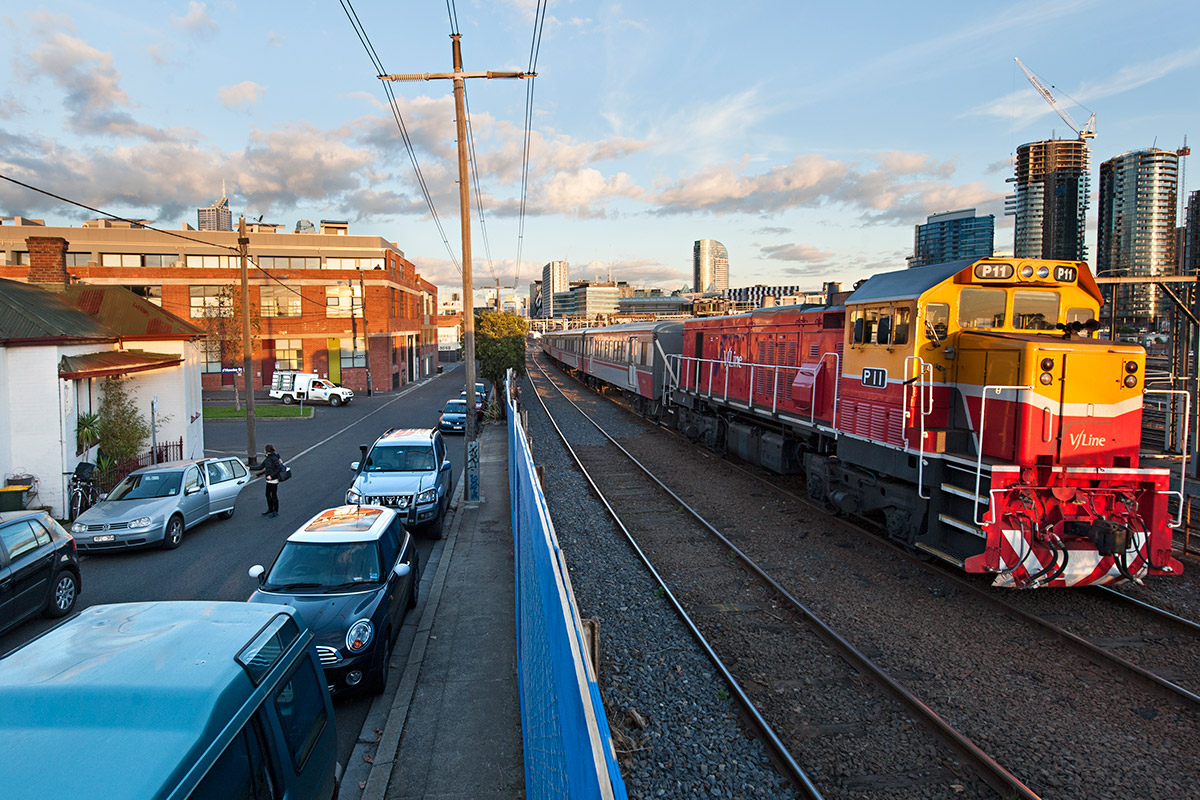 A regional train passing homes on Railway Place, West Melbourne as it approaches the West Melbourne rail flyover. The number of trains using the flyover has increased from about six trains a day in 2010 to over 180 trains a day in 2016. Homes that are less than 15-metres away from the nearest track are noticing a significant increase in vibration induced damage to houses, along with an increase in noise and air pollution.