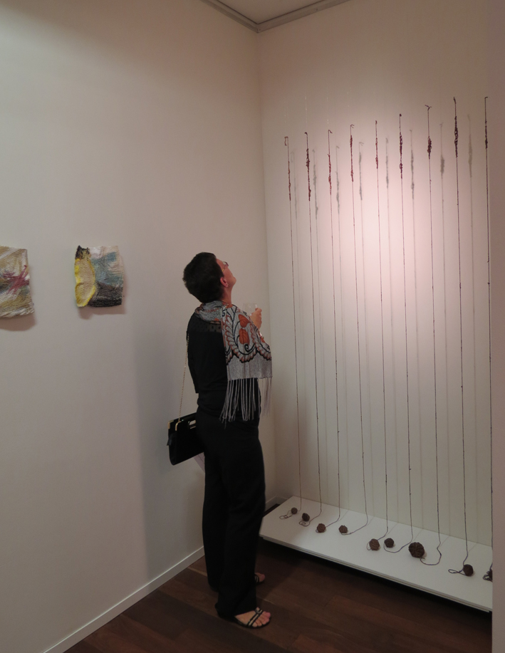 Exposition guest at the opening looking at work by Deb McArdle (wall work by Dionne Swift)
