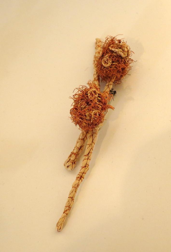 24. Cathy Rankin, Little Catabanksia, raffia, string, copper wire brooch, $35