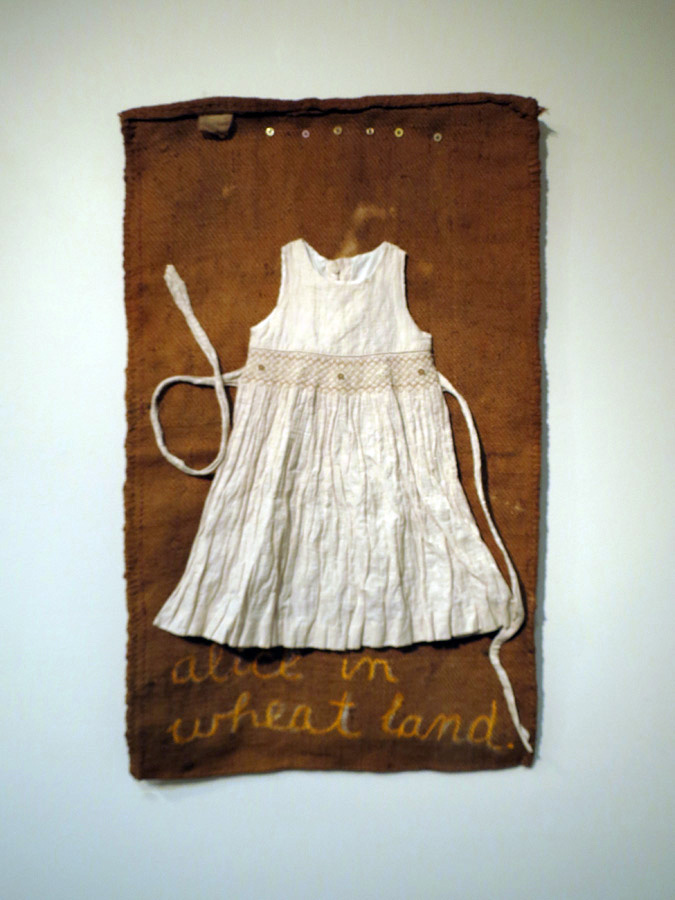 Nalda Searles,  Alice in Wheatland, homage to DH,  original wheat bag circa 1950's, child's hand-smocked dress with embroidery, (sourced from Kellerberrin op shop), hand stitching, oil pastel