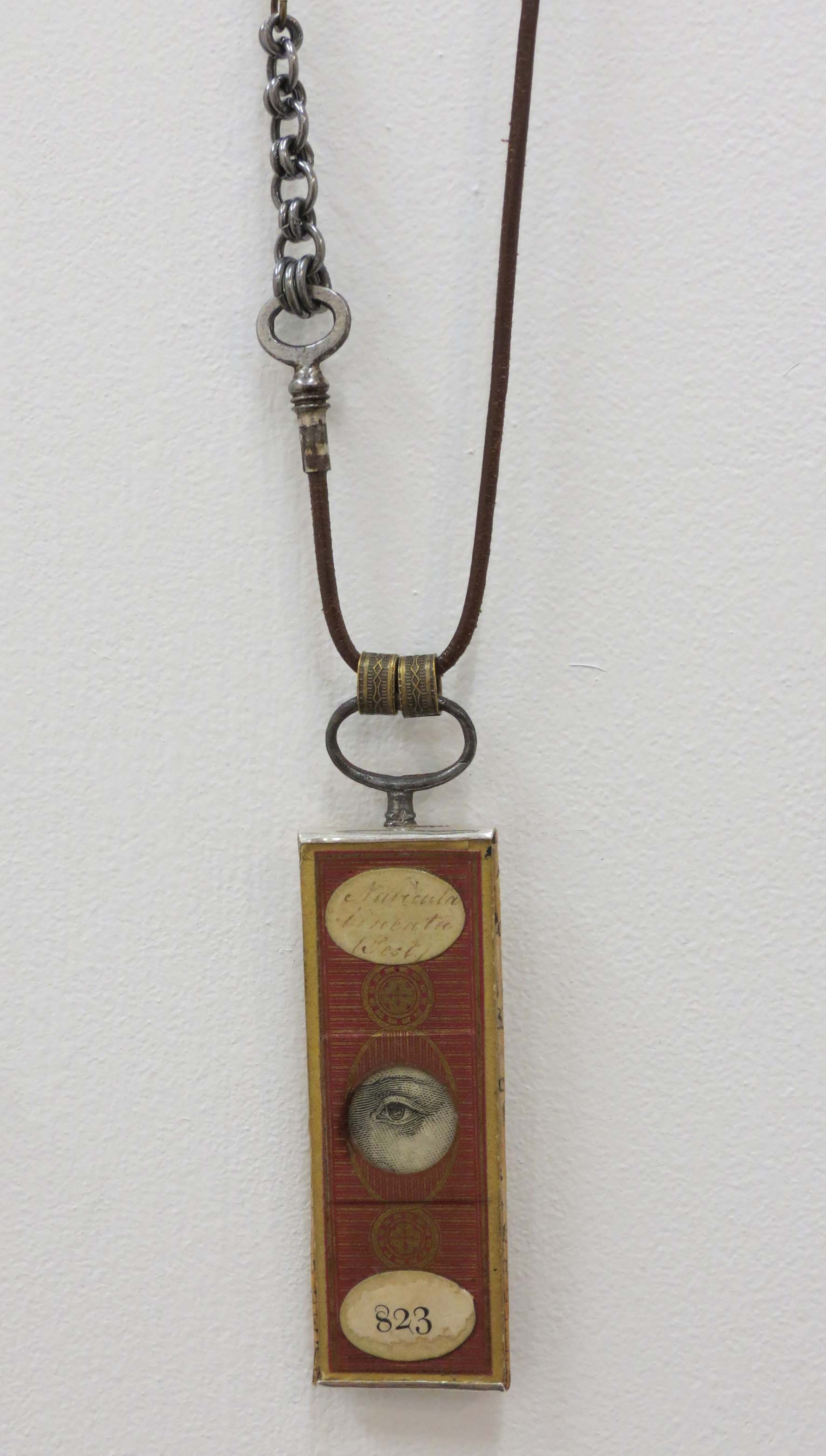 7. Kathy Aspinall, 'Oculus 823', 2018, Victorian papered slide, antique paper, leather, clock and watch keys, brass, silver, necklace, $495