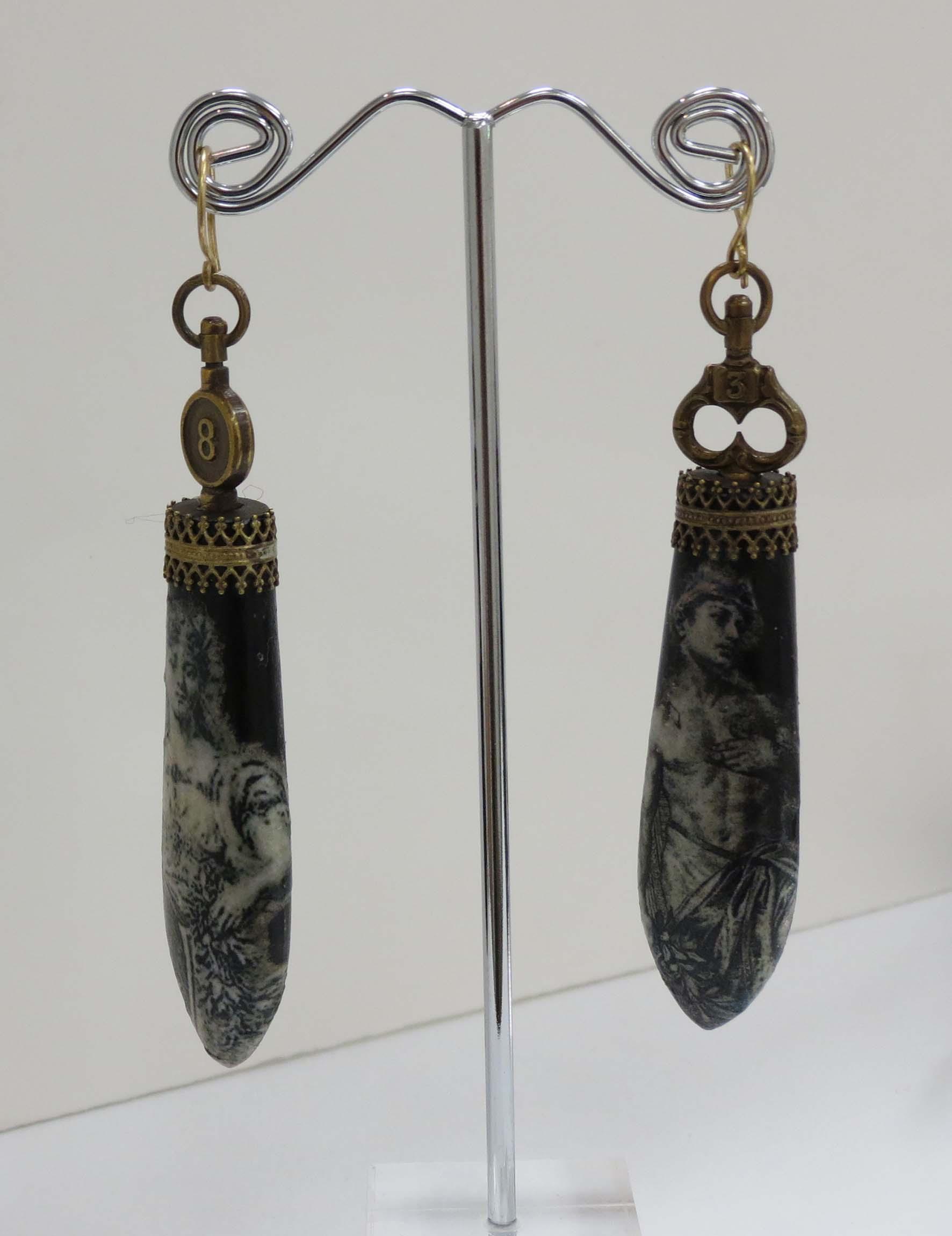 15. Kathy Aspinall, 'Ebony', 2018, Ebony, gallery wire, antique paper, watch keys, earrings, $300
