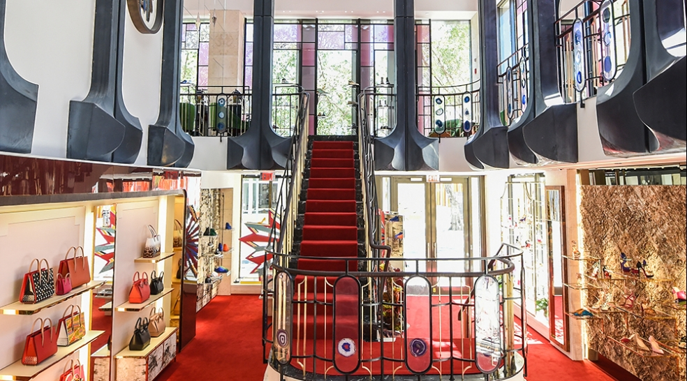 Christian Louboutin, Miami. Shoes and handbags are displayed whimsically. Merchandising supports the opulent interior design of red velvet staircases and stained glass.