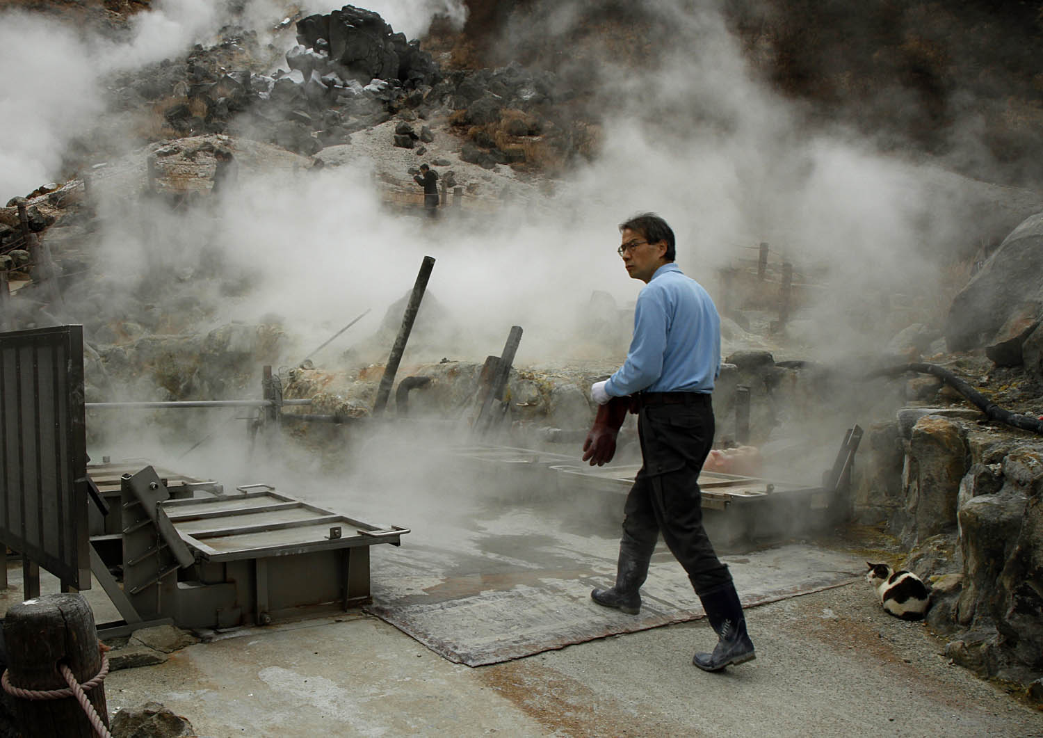 Steam surrounds a worker in Hakone, Japan, as he prepares to extract 黒玉子, or black eggs, from the sulfurous water of a mountain hot spring. The eggs boiled in the water take on a black color from the sulfur. According to legend, eating one of these eggs adds five years to your life.