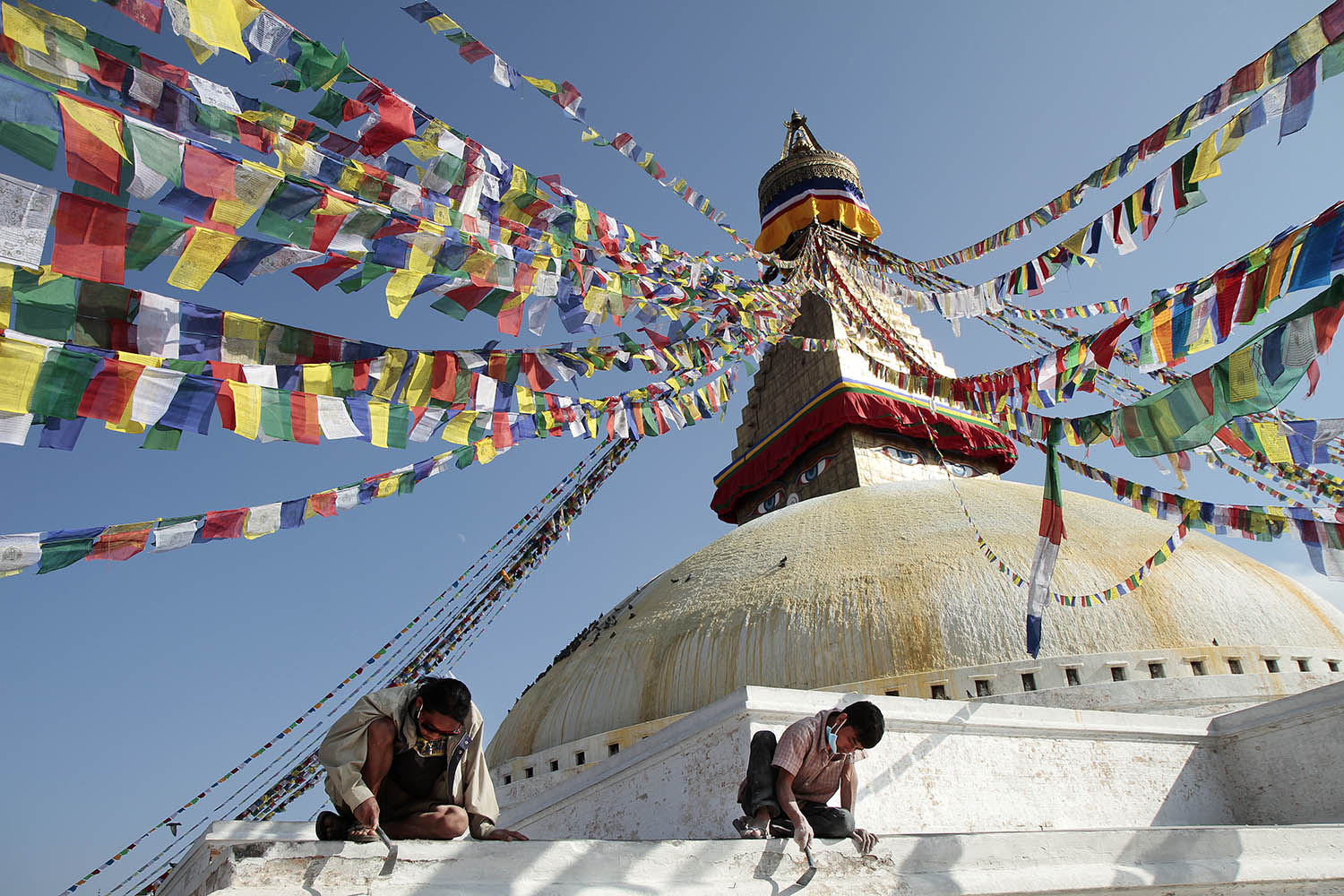 Workers at the Boudhanath in Kathmandu chip paint from the aging facade of the holy Buddhist site. The stupa, one of the largest in the world, had accumulated many layers of paint over its existence.