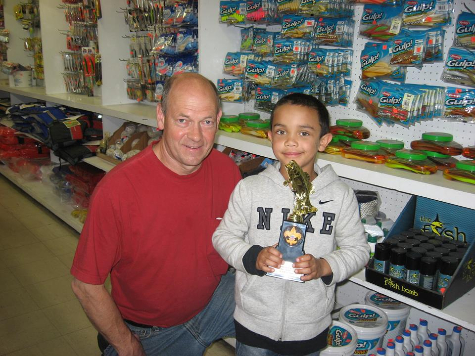 """Malachi Smith stopped by Wilcox Bait and Tackle to thank Tom Wilcox for providing bait for the Peninsula Scout Fishing Tournament. Malachi won a trophy for catching the heaviest fish, a 22.35 ounce, 15"""" largemouth bass."""