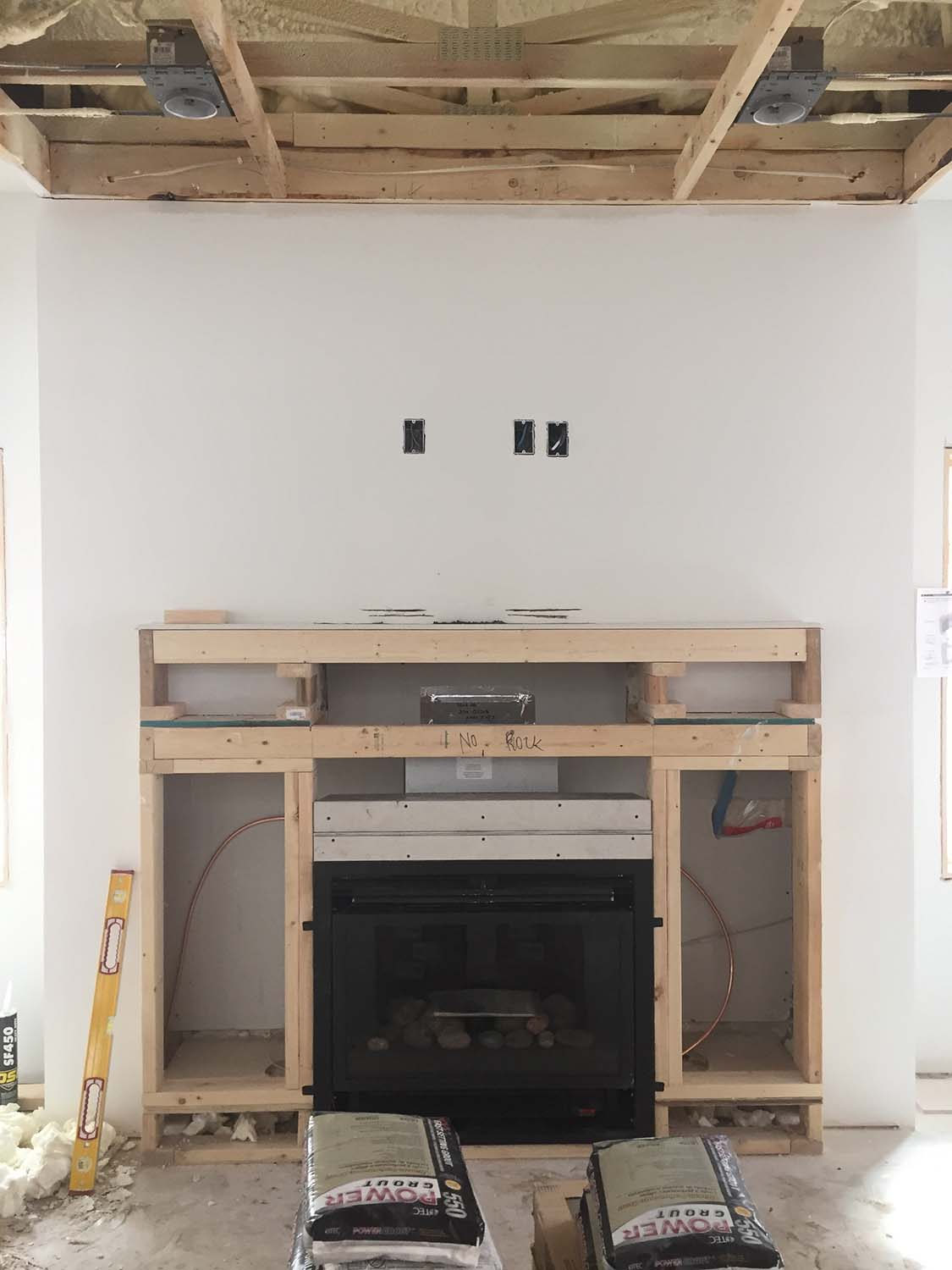 "We had to make a last-minute design change when we found that the fireplace required 10"" more headroom to provide a safe separation to combustibles.  Where the fireplace was to be 6"" above the floor and with a lower mantel, it's now down at floor level and the mantel has been raised up.  Who knows?  Maybe it will look better this way."