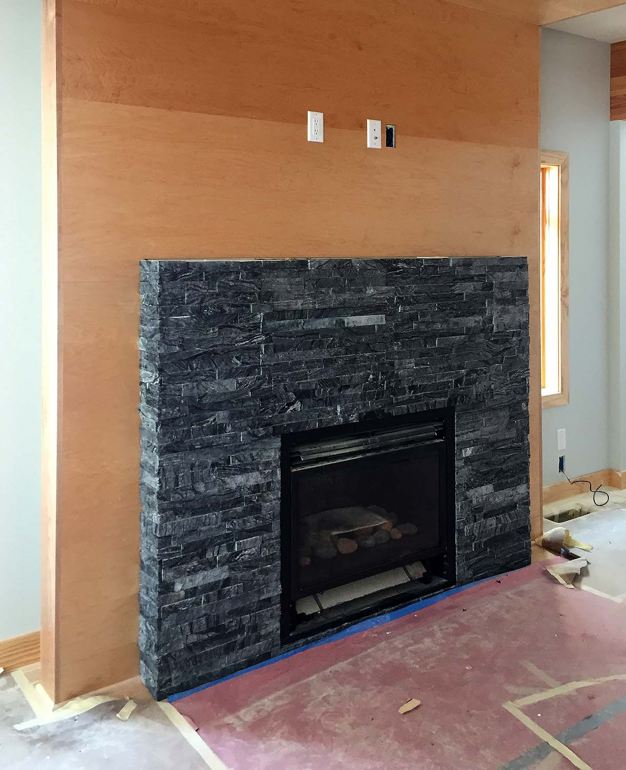 "The stone is from Rubble Tile: ""MSI Ledger Panel Split Face, Glacial Black"", ungrouted.  The wall panel beyond is clad in birch plywood."