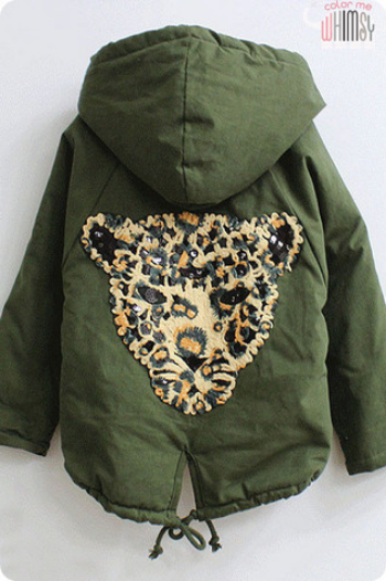 This  Color Me Whimsy Cheetah Army Jacket  is the Purr-fect option for your Little One. Not only is this Parka hip in washed-out green and slightly over-sized, but it is also on trend for Kids with the Oversized Cheetah Appliqué on the back with black sequin. This Cheetah Army Jacket is Unisex and would be just as cute on a boy as a girl!
