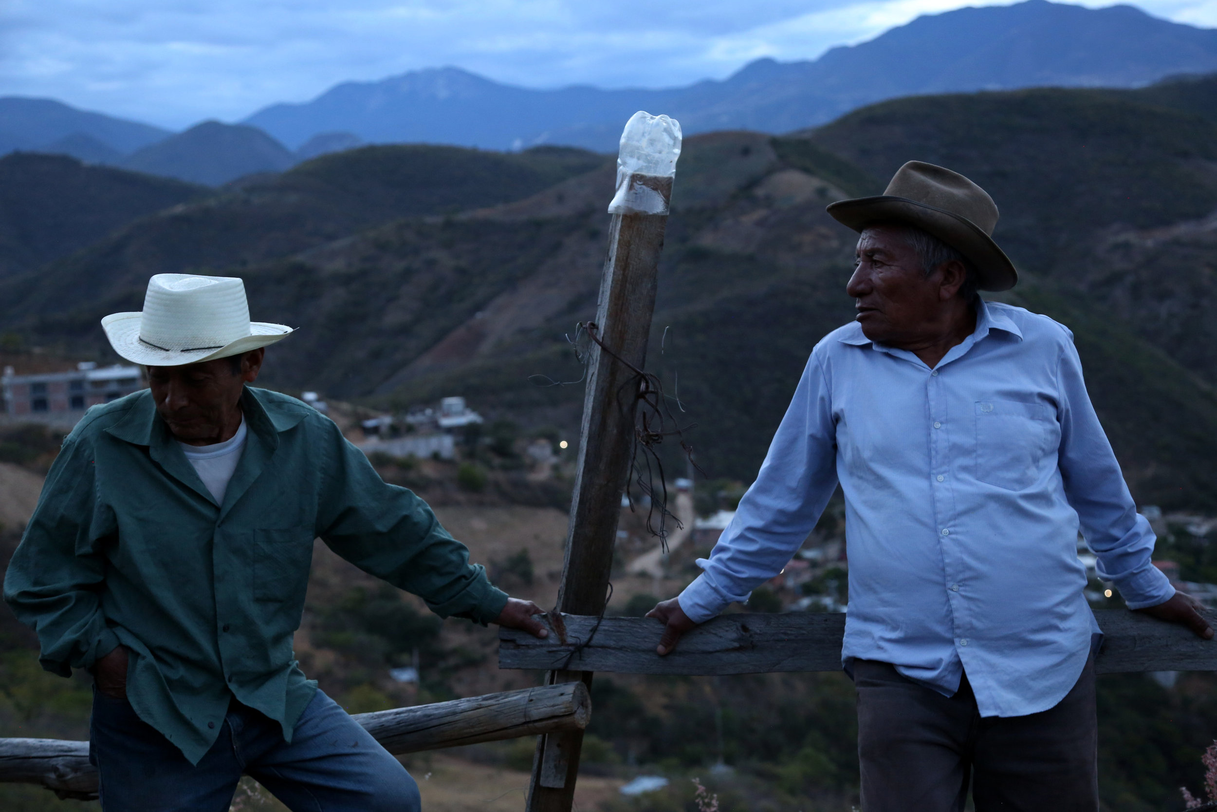 Arnulfo de los Angeles and Rodolfo Hernandez sit at the palenque that they share with Fortunate Angeles in  San Juan del Rio, Oaxaca.