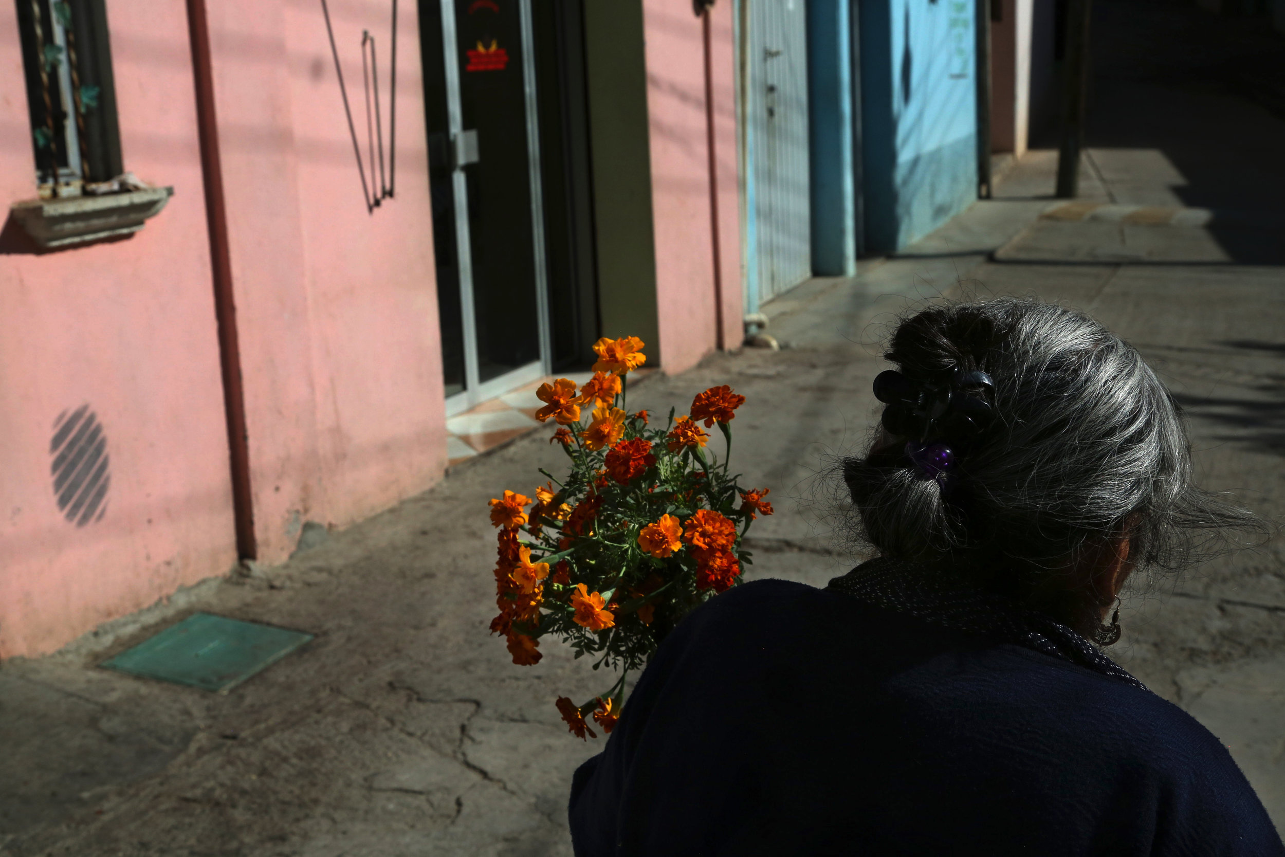 Teresa Raymundo carries flowers to a funeral in  San Juan del Rio, Oaxaca.