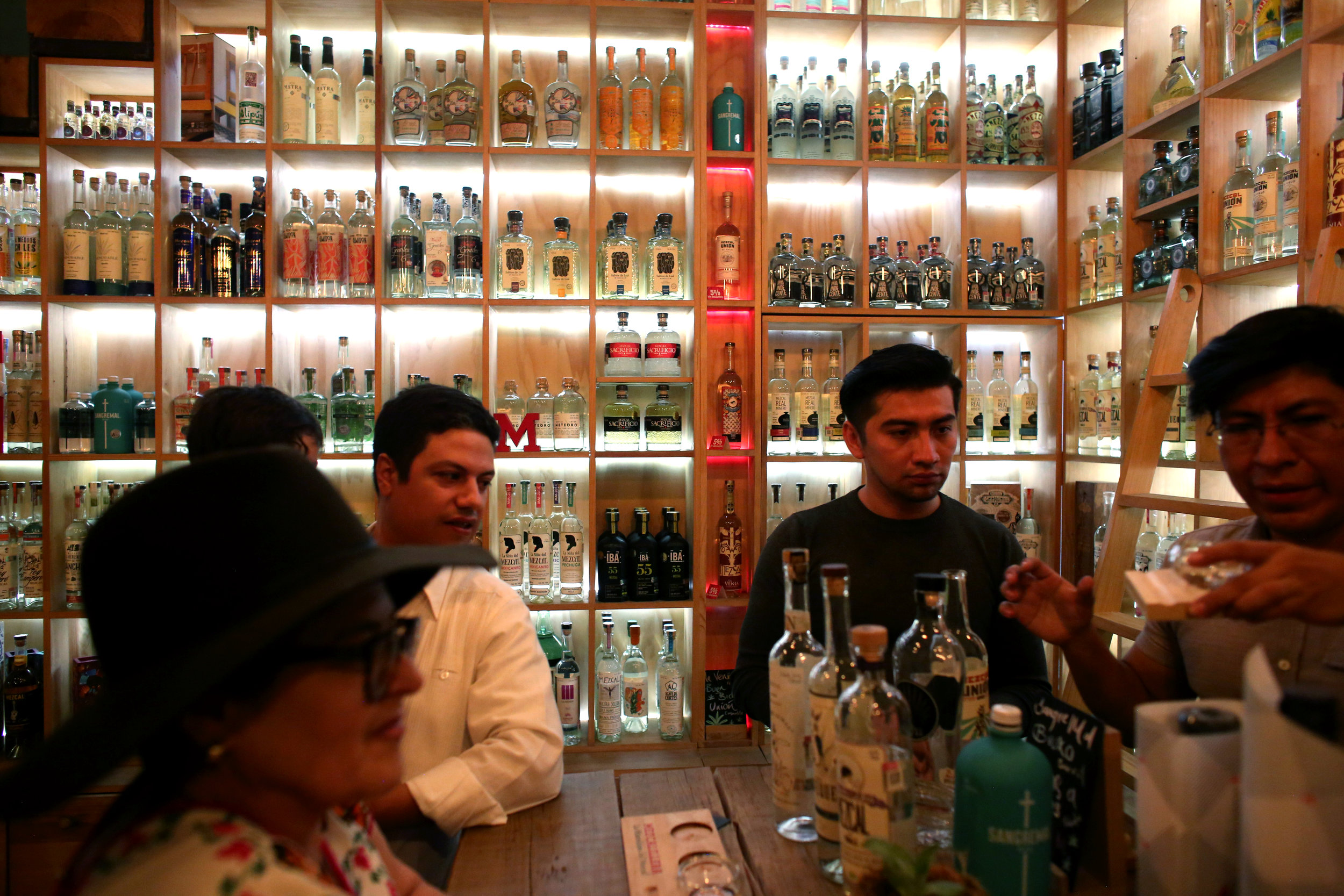 Tourists from Guadalajara sample mezcals at Mezcalilira in  Oaxaca City, Oaxaca.