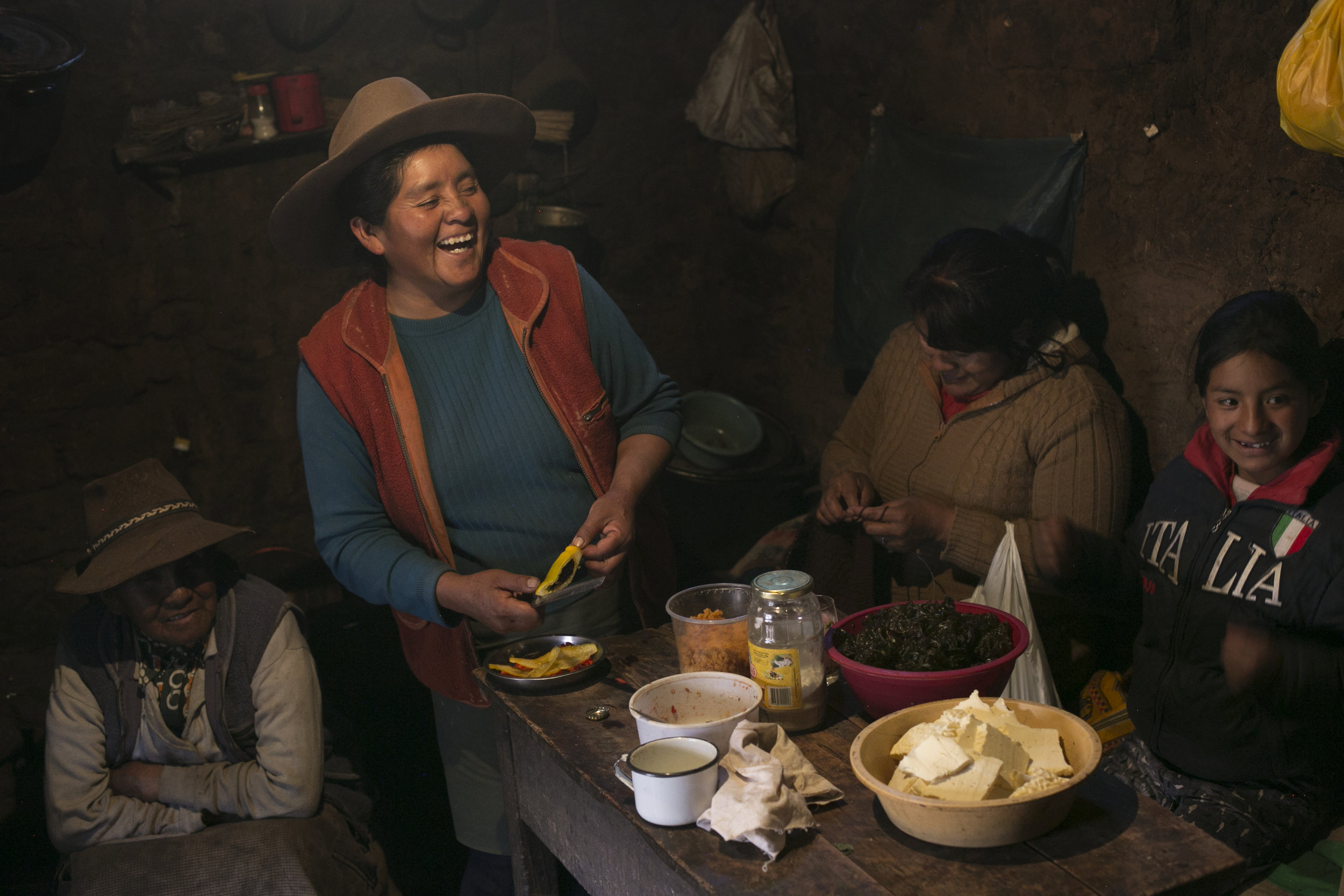 A smiling Claudia Corihuman prepares a birthday party for her mother (seated left) in Kacllaraccay, Peru.