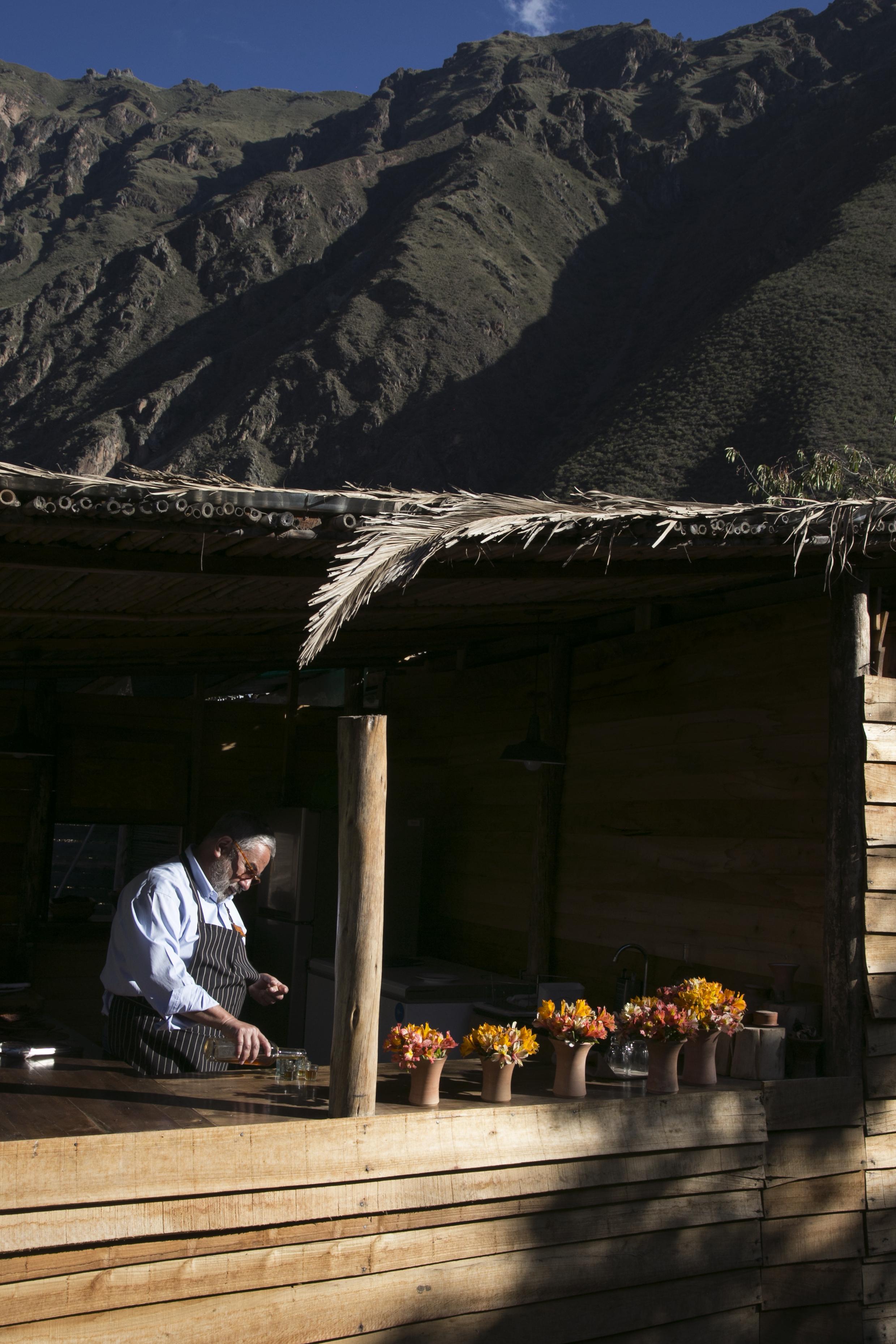 Gabriel Velasquez serves a pachamanca lunch in the organic garden at El Aubergue in Ollantaytambo, Peru.