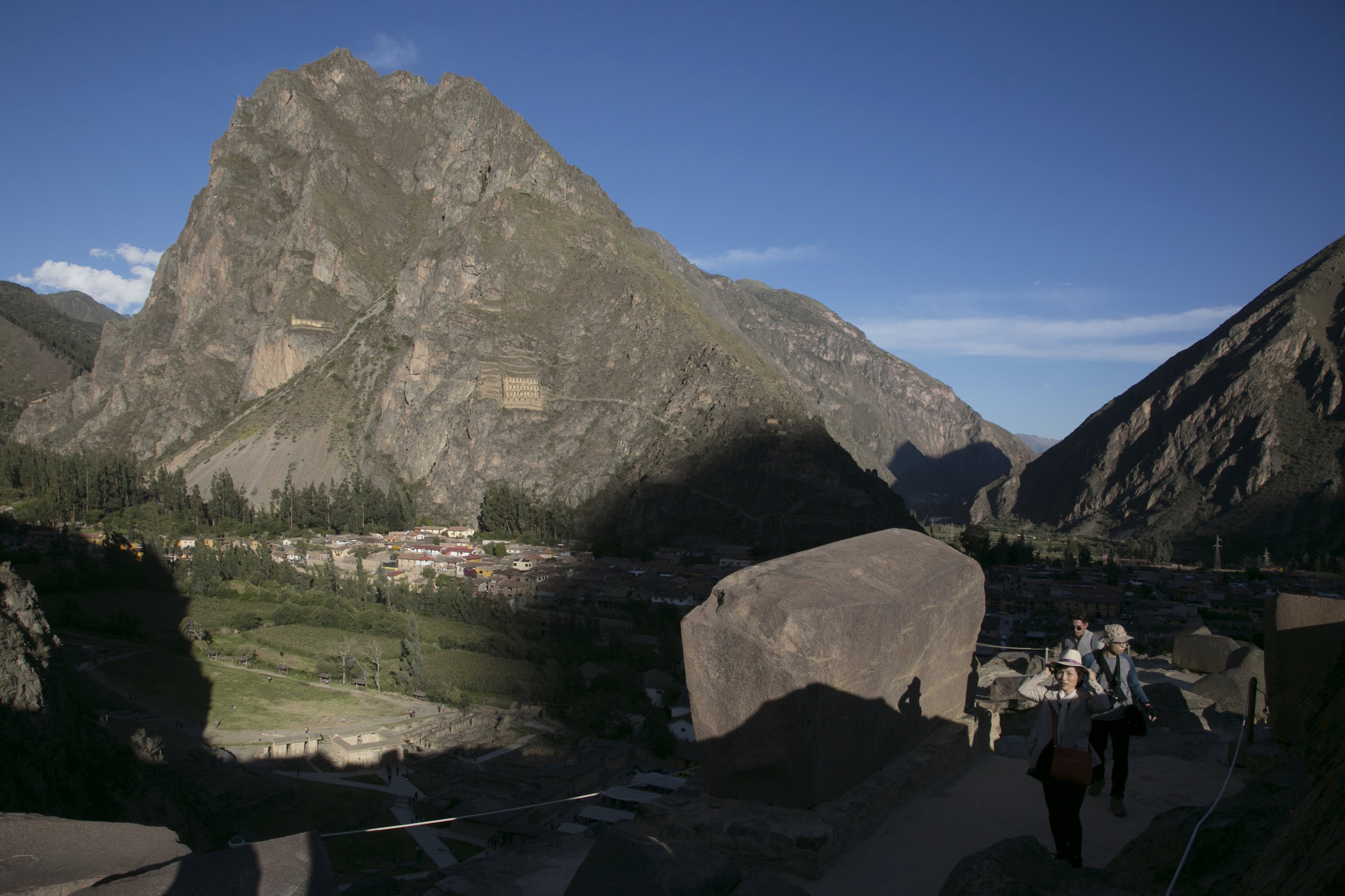 Tourists walk through the Inca terraces of Ollantaytambo, looking across to ancient granaries on the hill.  The Inca won a victory against the Spanish by fortifying the town and flooding the valley.
