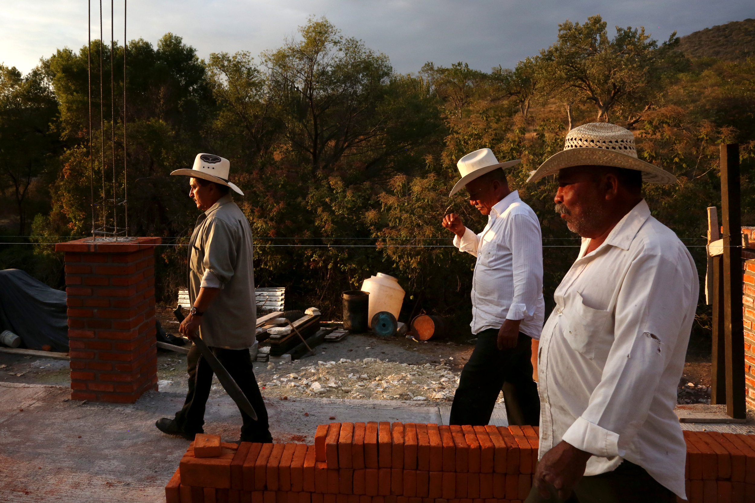 Mezcaleros walk through a palenque in construction in  Atlixo, Puebla.
