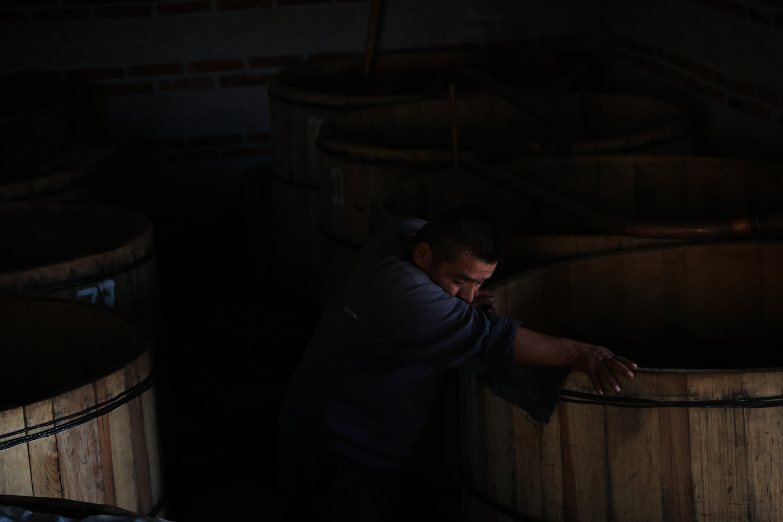 Fortunato Angeles rests on a fermentation tank at his palenque in  San Juan del Rio, Oaxaca.