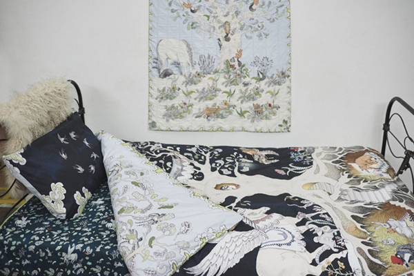 IMAGE 3: Close up of Forivor's Enchanted Forest Bedding  shown with the Enchanted Forest Quilted Blanket hanging on the wall and the Hidden Foxes and Tumbling Pegasus Blanket on the Bed.   Photo Credit: Jon Gorrigan for Forivor