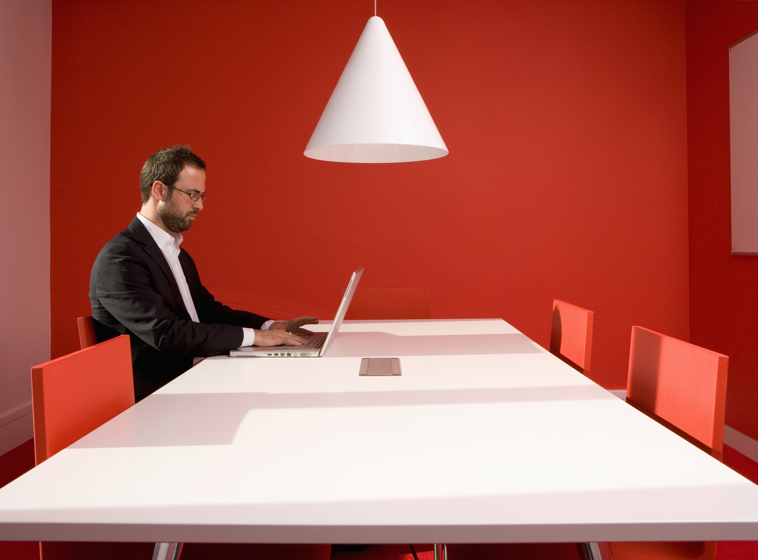 Executive using Laptop in Red and White Room