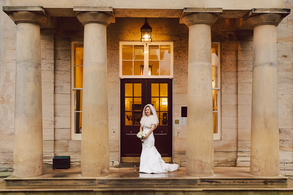 The bride hides away from the rain under the Portico, Linden Hall