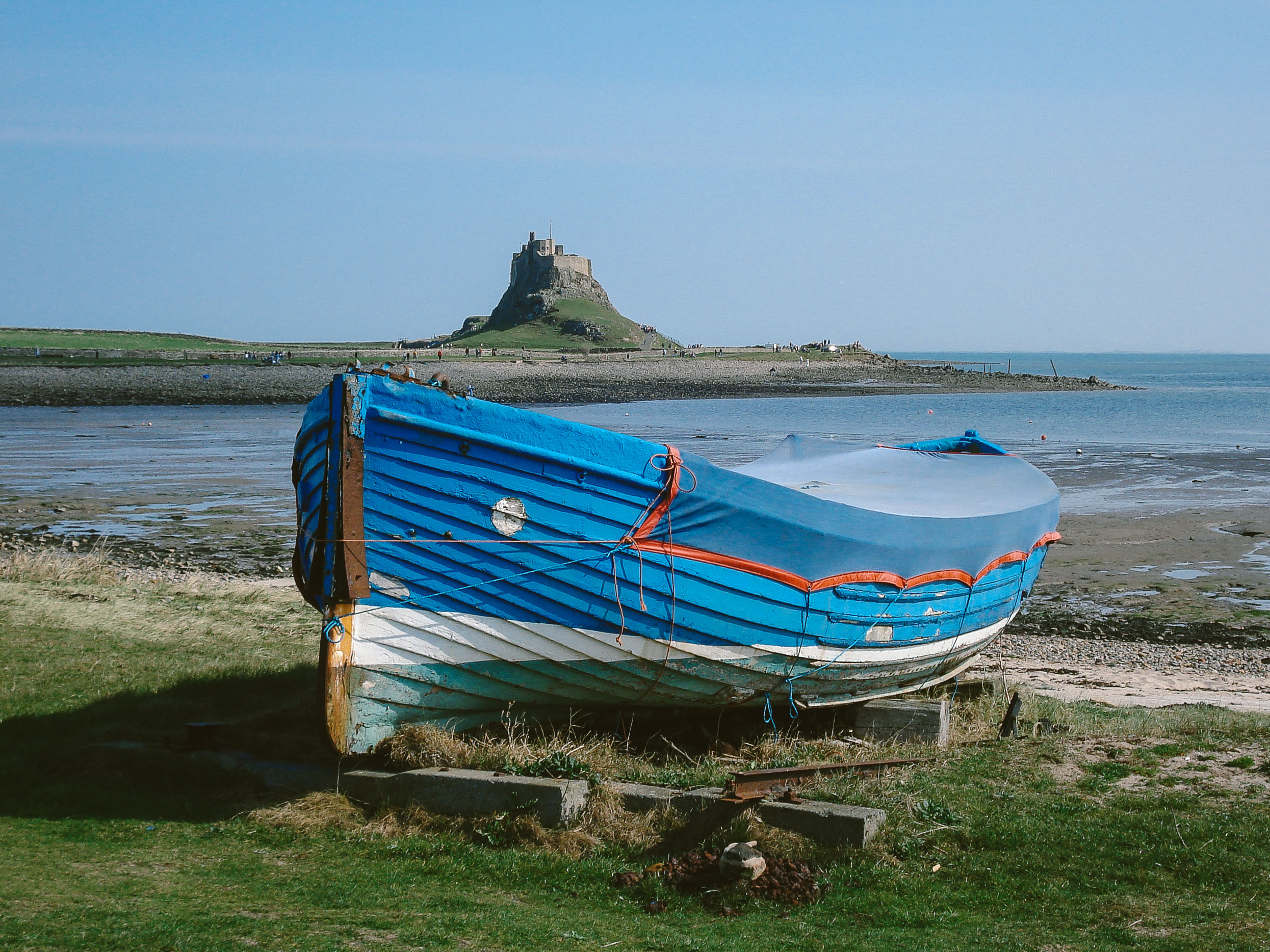 A fishing boat with Lindisfarne Castle in the background