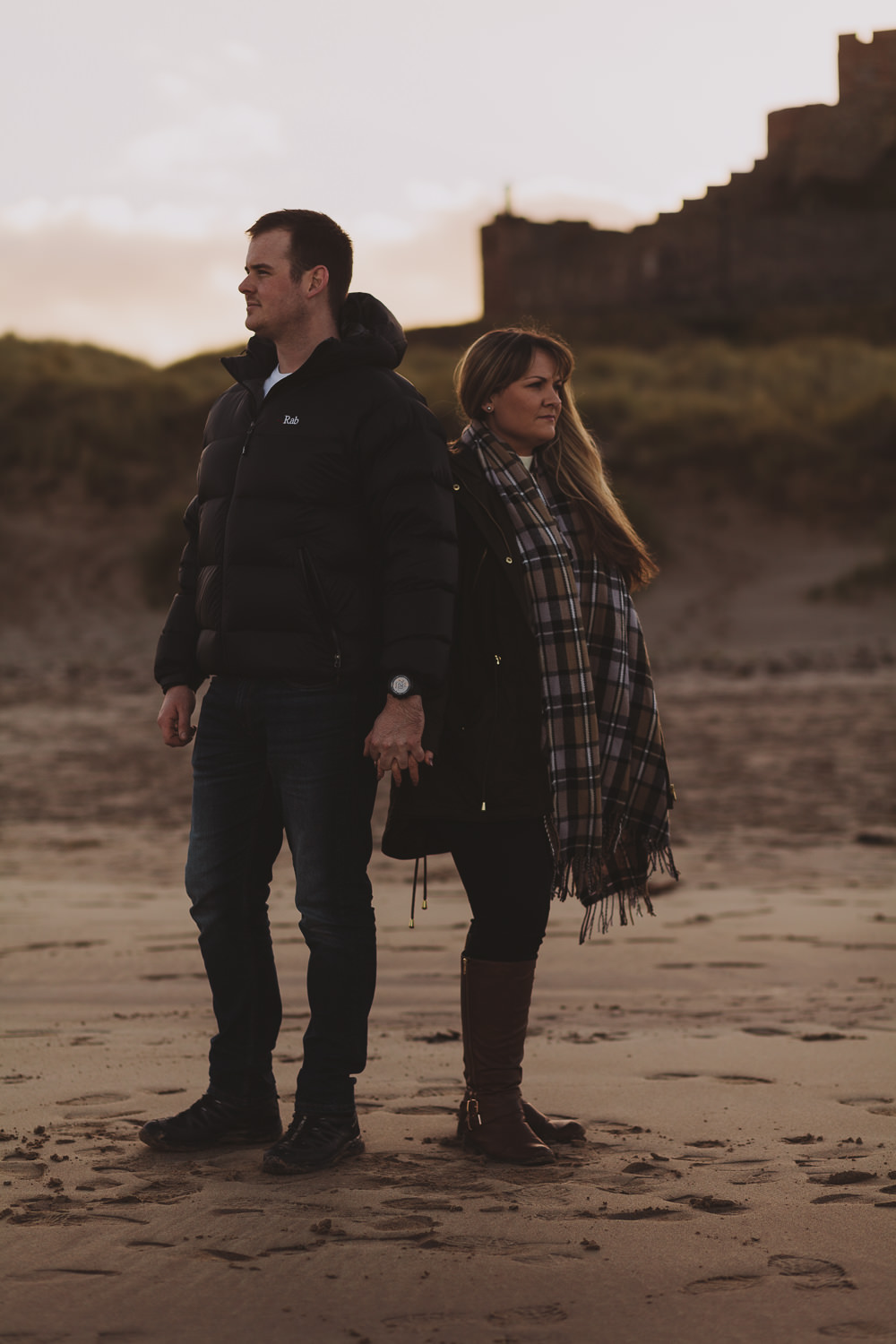 Callum and Dannielle looking out to sea on Bamburgh Beach, Northumberland Coast, with Bamburgh Castle behind them