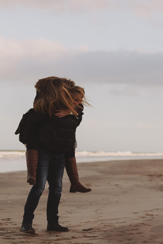 Callum giving Dannielle a piggyback on Bamburgh Beach, Northumberland Coast