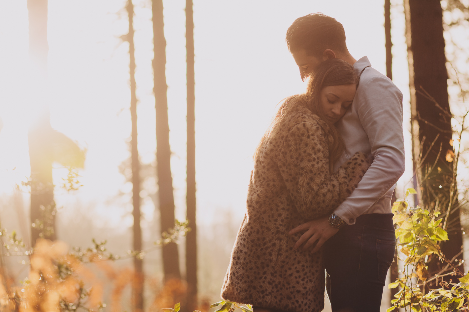 Engaged couple cuddling in a wood, bathed in sunlight in Newcastle upon Tyne
