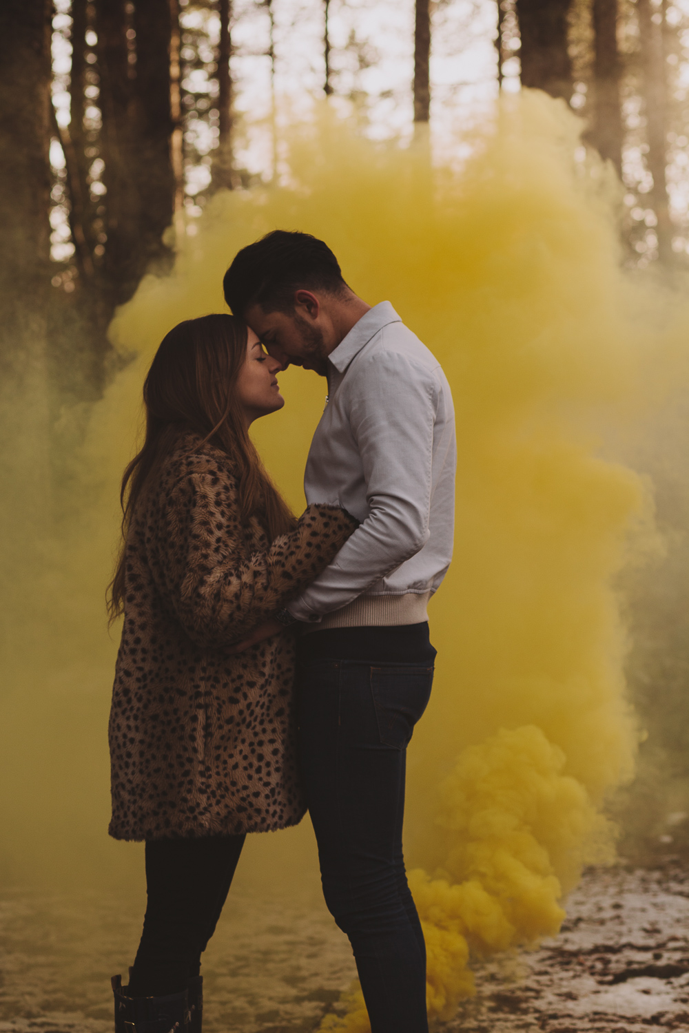 Engaged couple embracing in an old wood in Newcastle upon Tyne with smoke rising behind them