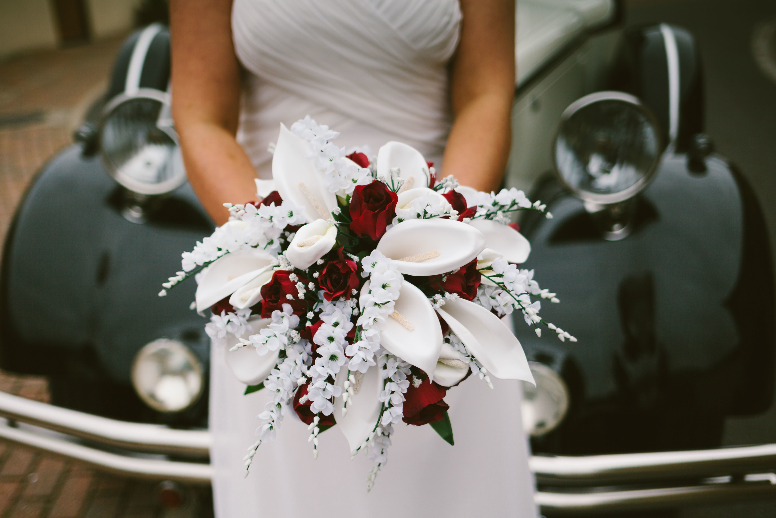 Durham Wedding Photographer South causey Inn Bride holding white and red bouquet in front of wedding car