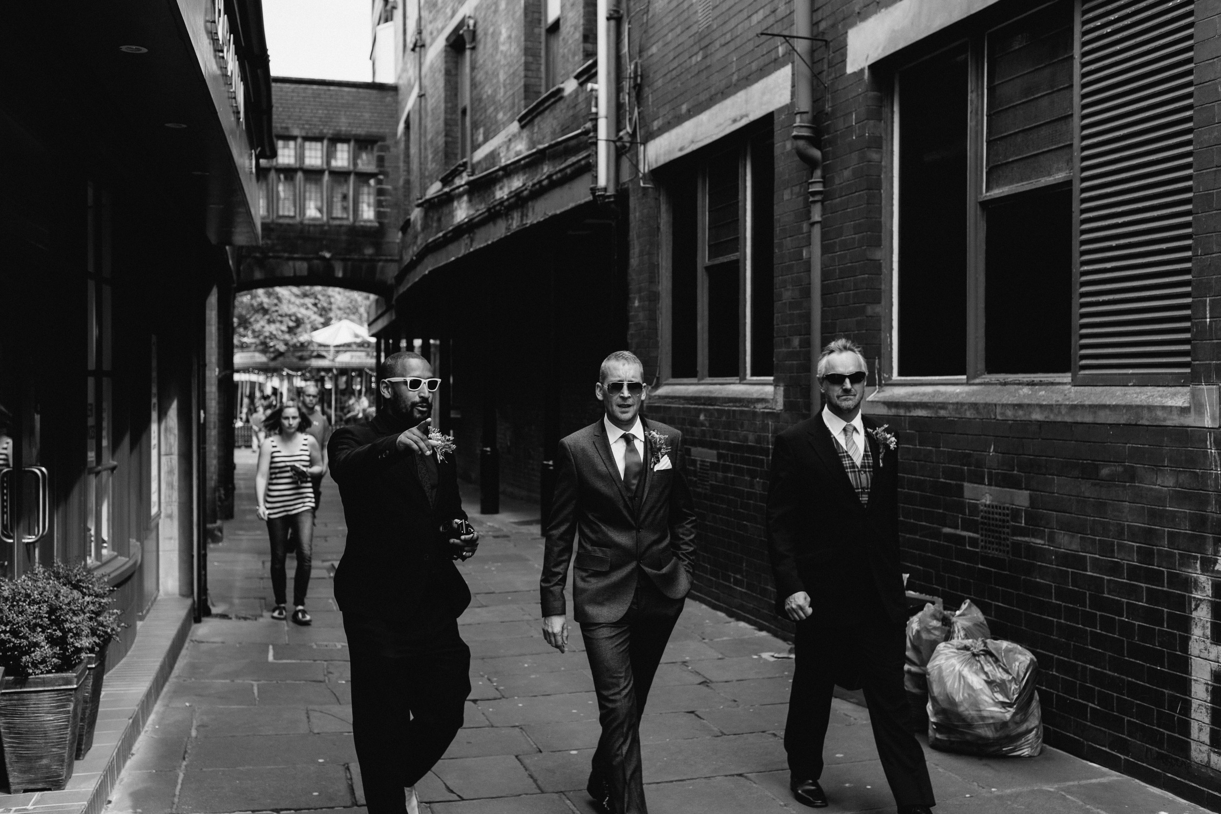 Martin and his groomsmen walk through a back alley in Carlisle while wearing sunglasses
