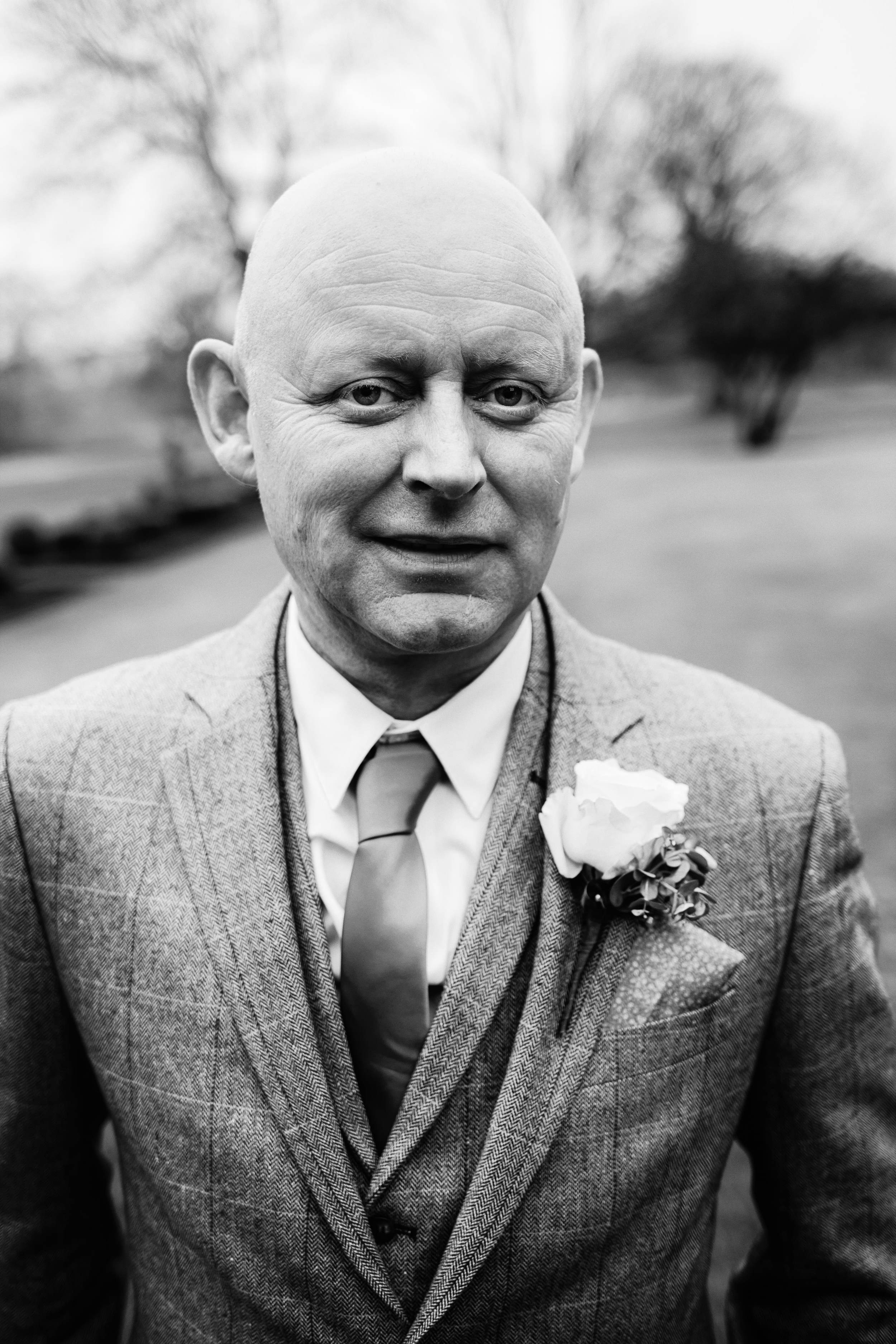 Black and white portrait of the groom in the grounds of Linden Hall, Northumberland