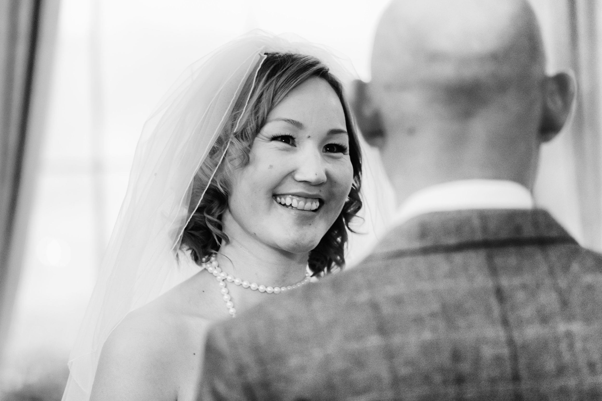 The bride smiles lovingly at the groom during their wedding ceremony at Linden Hall, Northumberland in this black and white photo