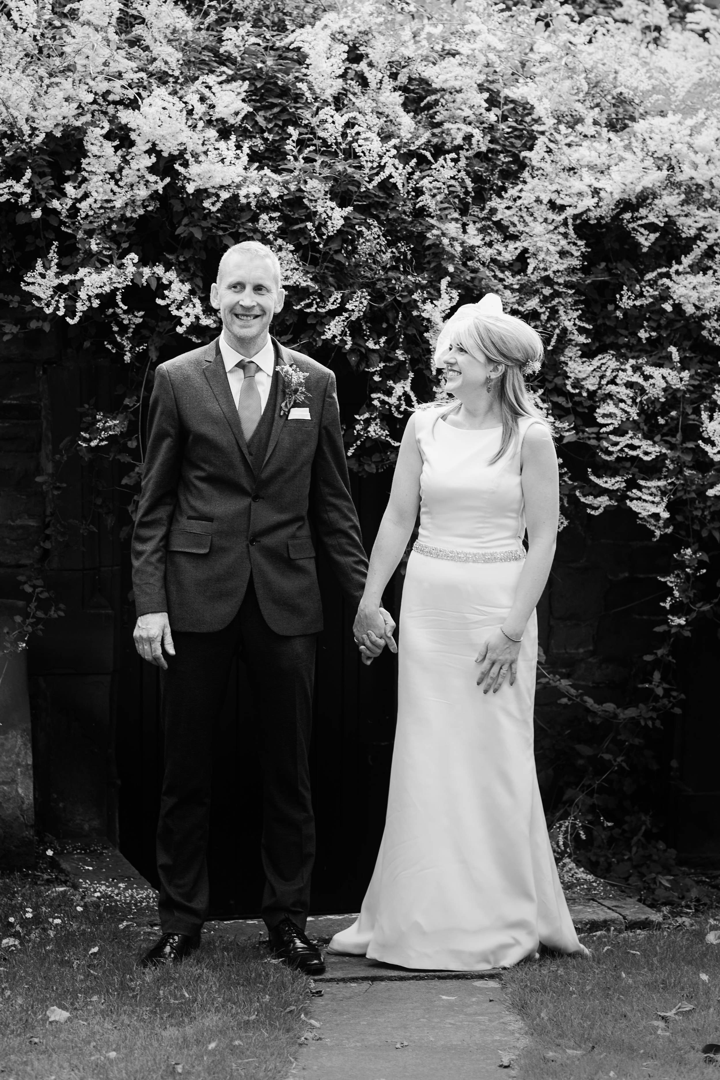 The bride and groom share a laugh in this black and white photograph taken at their weddding at Tithe Barn, Carlisle, Cumbria