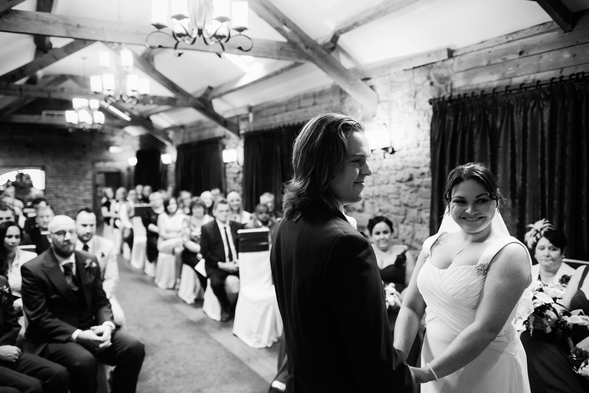 The bride and groom smile during their wedding ceremony at South Causey Inn, Durham